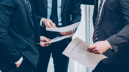 Partnership. Professional cooperation. Cropped shot of business men discussing contract terms.