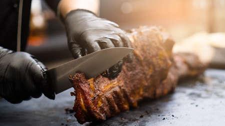 Cuisine de restaurant grill. Chef en gants de cuisine noirs à l'aide d'un couteau pour couper les côtes de porc fumées.