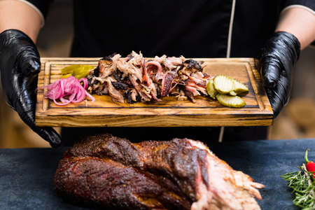 Grill restaurant kitchen. Chef hands in black cooking gloves holding smoked pulled pork with pickles on wooden board.