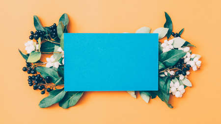 Party invitation. Blue mockup paper with black and white berries and green leaves arrangement. Peach background. Copy space. Stock Photo