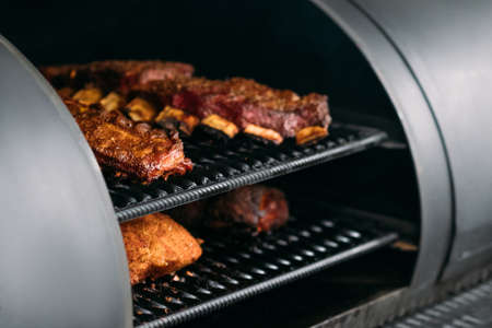 Professional kitchen appliance. Poultry, beef and pork meat, ribs cooked in BBQ smoker. Stock Photo