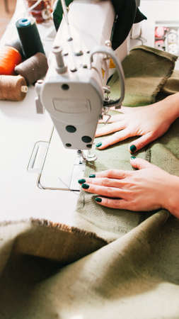 Upholstery manufacturing. Seamstress working with sewing machine in tailor studio.