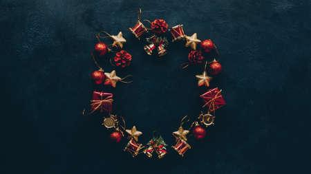 Nieuwjaar wenskaart. Bovenaanzicht van kerstkrans frame van ornamenten op donkere groenblauw blauwe achtergrond. Ruimte kopiëren.