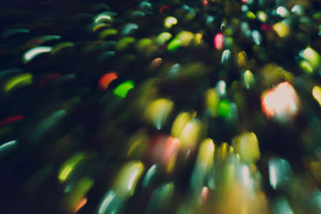 Blur green and yellow fairy lights. Multicolor smeared glowing spots. Dark abstract background. 免版税图像