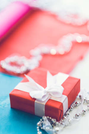 Vrouwen fancy cadeau. Close-up van rode doos met witte lintboog en juwelenstukken op onduidelijk beeldachtergrond. Ruimte kopiëren.