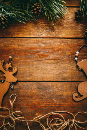 Christmas and New Year holiday. Festive wooden background. Flat lay of Santa sleigh, deer, pine, strobile. Frame, copy space.