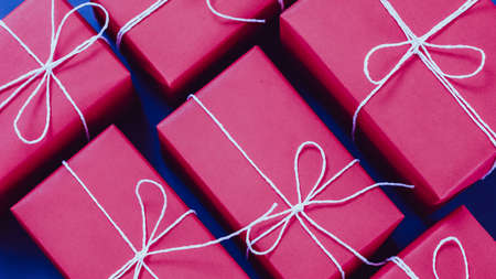 Holidays shopping. Handmade packaging. Top view of magenta paper gift boxes tied up with white cord. 스톡 콘텐츠