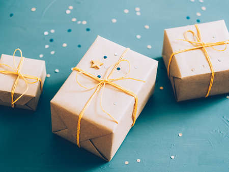 Holiday surprise. Top view of beige gift boxes on blur confetti pattern teal blue background. Copy space.
