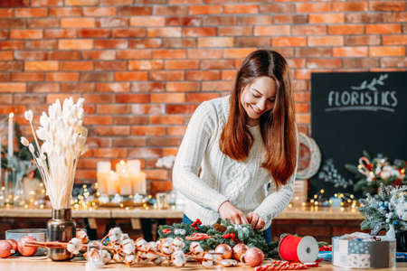 Florist workshop. Creative lady working on new festive winter decoration. Blur brick wall background. Copy space.
