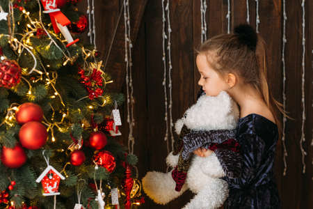 Christmas celebration. Side view of cute little girl standing with teddy bear at decorated fir tree, waiting for miracle.
