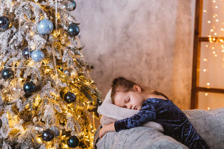 Christmas Eve. Tired little girl fallen asleep on couch while waiting for Santa with gifts at decorated fir tree at home.