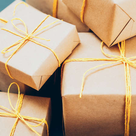 Holidays shopping. Handmade packaging. Stack of beige paper gift boxes tied up with yellow cord.