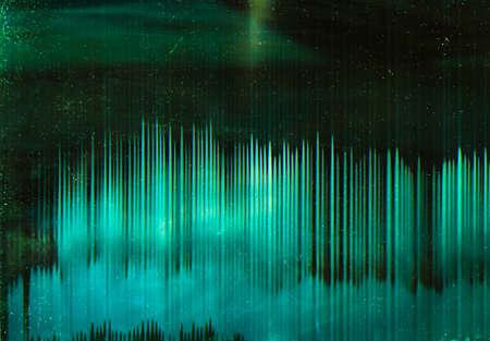 Green distressed filmstrip. Dust pattern. Lens flare glow on dark background.