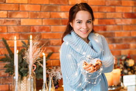 Festive interior decor. Portrait of happy lady holding fairy lights. Blur brick wall background. Copy space.