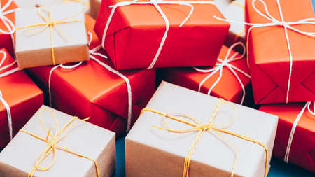 Holidays shopping. Handmade packaging. Closeup of beige and red paper gift boxes stack.
