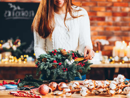 Florist creative business. Cropped shot of lady decorating green fir tree wreath with orange slice. Blur brick wall background.