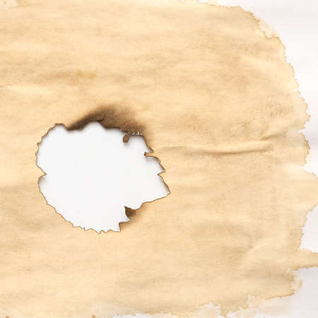 Stained beige paper with burnt hole on white background. Grunge abstract design. Copy space. Stock Photo