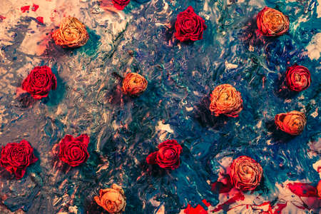 Abstract floral art background. Flat lay arrangement of red and orange dried rose buds on smeared blue paint.