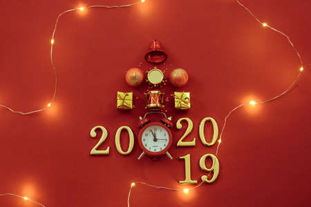 New Year celebration time 2019 - 2020. Flat lay of Christmas ornaments, retro clock, lights and numbers on red background.