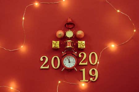 Tiempo de celebración de año nuevo 2019 - 2020. Sentar planas de adornos navideños, reloj retro, luces y números sobre fondo rojo.