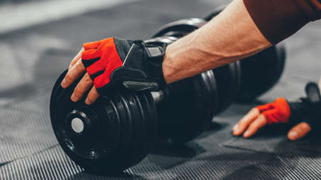 Crossfit workout. Male athlete in sport gloves choosing dumbbell for training at gym. Copy space. Stock Photo