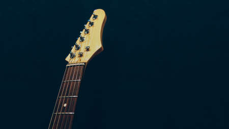 Professional music class. Electric guitar headstock over dark background. Copy space. Stock Photo