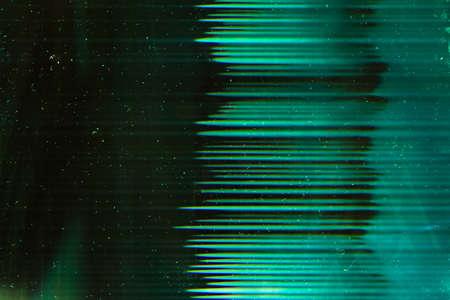 Green dusty overlay. Old filmstrip. Glowing flecks scratches on dark background. Stock Photo