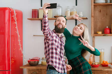 Winter holidays fun celebration. Cheerful couple using smartphone camera to take selfie in modern kitchen with fairy lights. Фото со стока