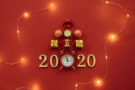 New Year celebration time 2020. Flat lay of Christmas ornaments, retro clock, lights and numbers on red background.