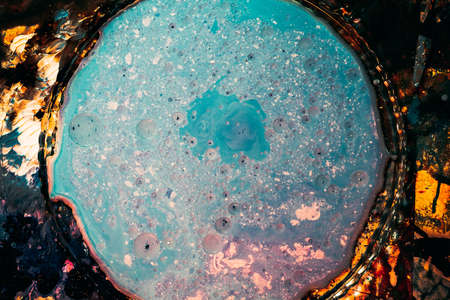 Abstract art background. Blue colored enamel in clear glass plate. Bubbled textured surface.