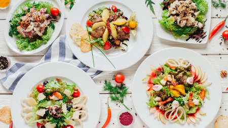 Festive banquet table. Top view of various salads with vegetables and seafood on white wooden background.