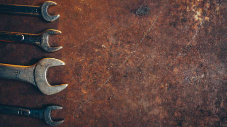 Automobile repair shop. Professional wrench set on rusty dark metal background. Copy space.