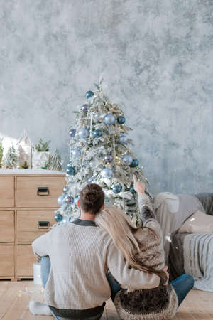 Family Christmas. Back view of couple sitting on floor embracing, looking at fir tree they decorated. Cozy festive home interior.