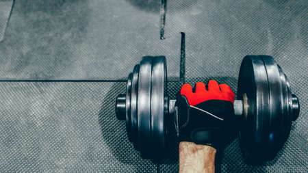 Crossfit workout. Strong male athlete hand holding dumbbell over gray floor at gym. Copy space.