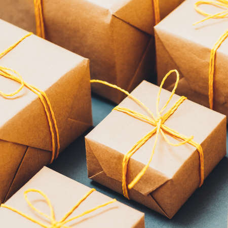 Online shopping. Seasonal sale. Cropped closeup of beige paper boxes on blue sage background.