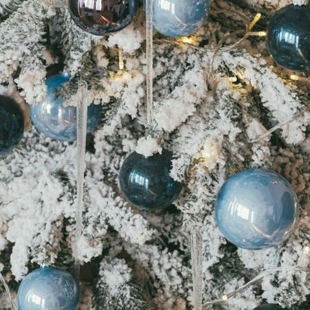 Christmas greeting card. Closeup of fir tree covered with white snow, adorned with blue glass ball ornaments and fairy lights.