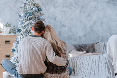 Romantic winter holidays. Back view of peaceful couple sitting on floor embracing, looking at fir tree they decorated. 写真素材