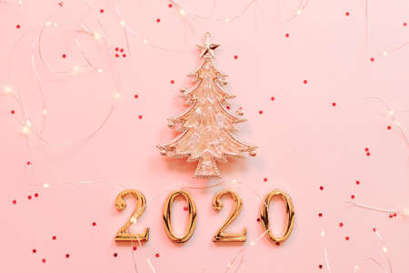 New Year 2020 greeting card. Flat lay of golden fir tree ornament and string lights on star pattern pink background. Copy space.