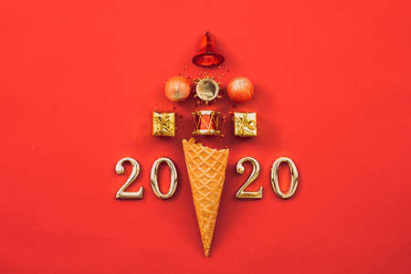 Happy New Year 2020. Abstract Christmas tree arrangement in ice cream waffle cone and numbers on red background. Copy space.