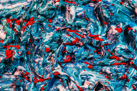 Colorful abstract art background. Blue and white acrylic paint mix with vibrant red splash.