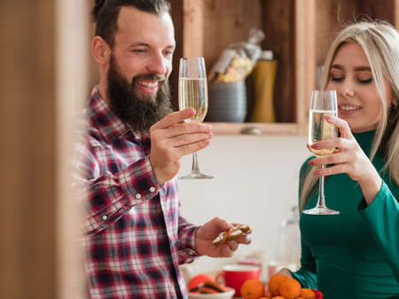 Happy New Year. Cheerful couple drinking champagne in modern kitchen, celebrating winter holidays at home.