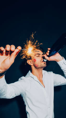 New year party. Wasted guy with lipstick kisses on his cheek dancing with sparkler, drinking wine from bottle.