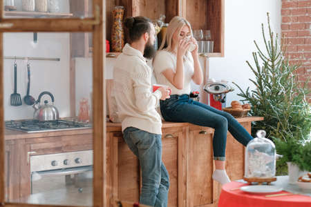 Family winter morning leisure. Couple drinking coffee in modern kitchen with wooden furniture. Green fir tree in background.