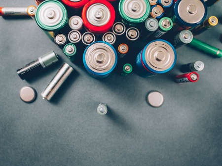 Waste recycling. Colorful batteries, accumulators Gray background