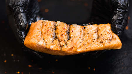 Steakhouse and seafood restaurant. Closeup of juicy piece of seasoned smoked salmon fillet in chef hands in black cooking gloves.