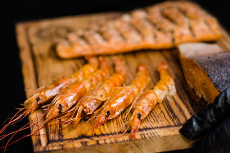 Mediterranean cuisine. Closeup of langoustines and smoked salmon fillet served on wooden board. Stockfoto