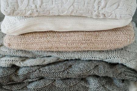 Winter-Heimtextilien. Kuschelig warme Strickdecke und weicher Kissenstapel. Standard-Bild