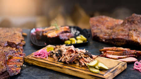 Grill restaurant. Closeup of smoked pulled pork served with pickles on wooden board. Roasted meat and ribs in background. Zdjęcie Seryjne