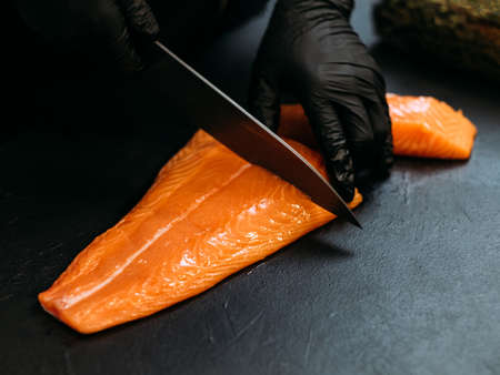 Seafood restaurant. Closeup of chef hands using knife to cut fresh salmon fillet. Copy space.