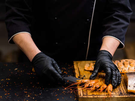 Steakhouse and seafood restaurant. Chef in black cooking gloves serving smoked langoustines on wooden board. Stock Photo